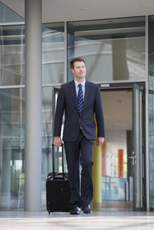 Germany, Hannover, Businessman walking with briefcase at terminal - KFF000082