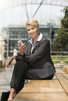 Germany, Hannover, Portrait of businesswoman sitting on bench with smart phone, smiling - KFF000195