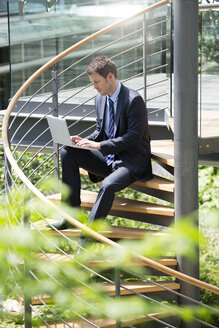 Germany, Hannover, Businessman sitting on stairs and using laptop - KFF000182