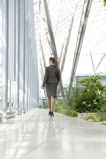 Businesswoman walking in modern courtyard - KFF000144