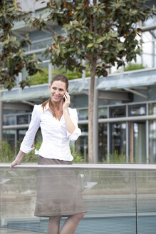 Businesswoman using cell phone on footbridge - KFF000164