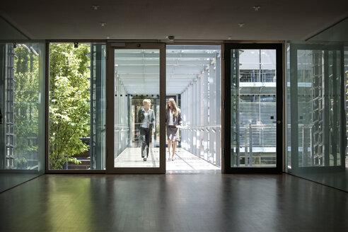 Two businesswomen talking in office building - KFF000126