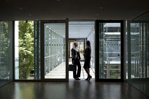 Two businesswomen talking in office building - KFF000167