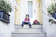 Germany, North Rhine Westphalia, Cologne, Portrait of girl waiting at school, smiling - FMKYF000488