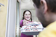 Germany, North Rhine Westphalia, Cologne, Girl taking pizza boxes from delivery man, smiling - FMKYF000485