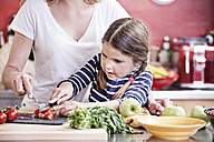 Germany, North Rhine Westphalia, Cologne, Mother and daughter cutting vegetables - FMKYF000471
