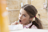 Germany, North Rhine Westphalia, Cologne, Girl brushing teeth in bathroom - FMKYF000468