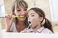 Germany, North Rhine Westphalia, Cologne, Mother and daughter brushing teeth in bathroom - FMKYF000465
