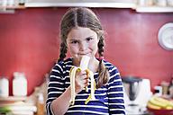 Germany, North Rhine Westphalia, Cologne, Portrait of girl eating banana in kitchen - FMKYF000456