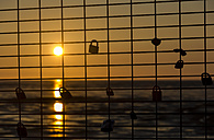 Germany, Lower Saxony, Lovelocks locked on grills at sunset - SJF000039