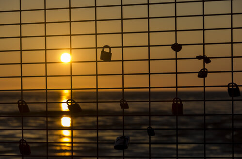 Germany, Lower Saxony, Lovelocks locked on grills at sunset - SJF000039