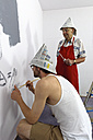 Germany, Grandfather and grandson painting wall - LAF000121