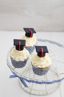 Graduation cupcakes with vanila frosting on cake stand, close up - ECF000282