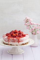Strawberry cheesecake with fresh strawberries and redcurrants on wooden table, close up - ECF000293
