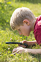 Germany, Bavaria, Boy looking through magnifying glass in garden - SARF000077