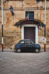 Italy, Apulia, Old Fiat 500 parked under flag - DIK000060
