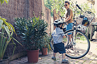 Germany, Bonn, Little boy and father getting ready for a bicycle tour - MF000605