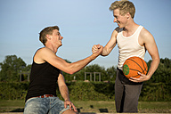 Germany, Two young men meeting up to play basketball - GDF000142