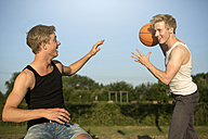 Germany, Two young man meeting up to play basketball - GDF000204