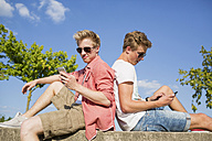 Germany, Two young men sitting on wall using their smart phones - GDF000147