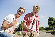 Germany, Young man is making rock' roll sigh, while friend is looking away - GDF000161