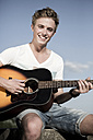 Germany, Young man playing guitar in park - GDF000176