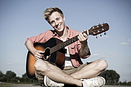Germany, Young man playing guitar in park - GDF000179