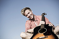 Germany, Young man holding guitar, smiling - GDF000183
