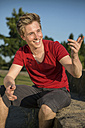 Germany, Young man sitting in park, gesturing - GDF000187