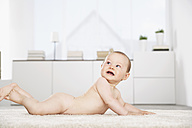 Germany, North Rhine Westphalia, Cologne, Baby girl lying on carpet - PDF000365