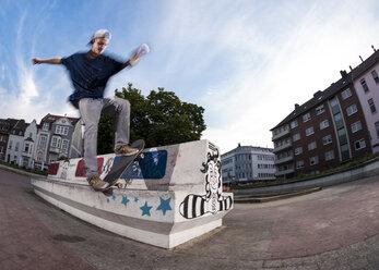 Germany, North Rhine Westphalia, Moenchengladbach, Young man skating on public place - KJ000250