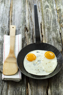 Fried eggs in pan with wooden spoon on napkin - OD000291