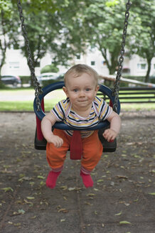 Germany, Hesse, Frankfurt, Portrait of baby boy swinging - MUF001336