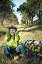 Germany, Saxony, Boy sitting with basket full of apples - MJF000314
