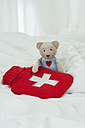 Germany, Bavaria, Teddy bear with hot water bottle on bed - CRF002458
