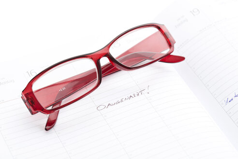 Reading glasses on appointment calendar, close up - MAEF007179
