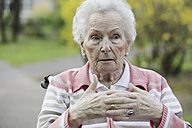 Germany, North Rhine Westphalia, Cologne, Senior woman sitting on wheelchair, looking away - JAT000217