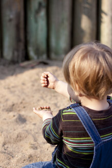 Germany, Kiel, girl plays with sand on playground, from behind - JFEF000169