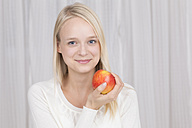 Portrait of young woman holding red apple, smiling - DRF000129