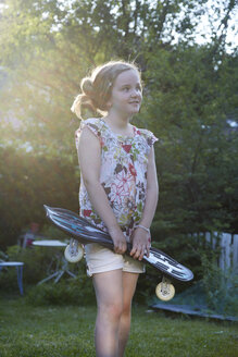 Germany, Girl holding waveboard and looking away - DHL000011