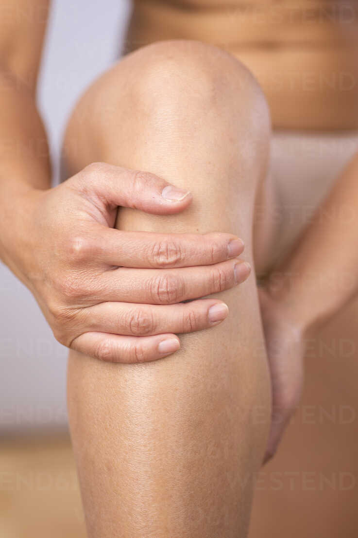 Germany, Freiburg, Mid adult woman holding her knee, close up - DRF000098 - Stefan Rupp/Westend61