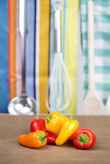 Germany, Freiburg,Yellow, orange and red bell peppers on chopping board, close up - DRF000106