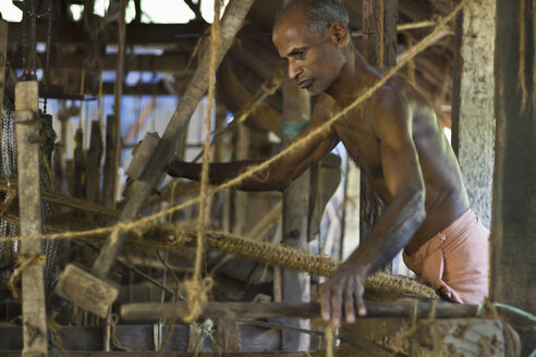 India, Kerala, Kochi, Man working at coconut doormat factory - MBE000652