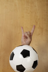 Mature man gesturing hand sign on soccer football, close up - KRPF000023