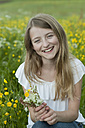 Germany, Bavaria, Portrait of girl holding flowers, smiling - CRF002465