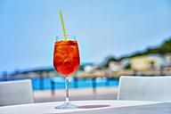 Italy, Glass of Aperol spritz drink at street cafe near beach - DIKF000068