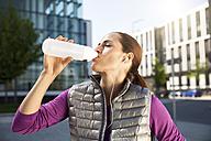 Athletic brunette woman drinking from bottle - SU000005