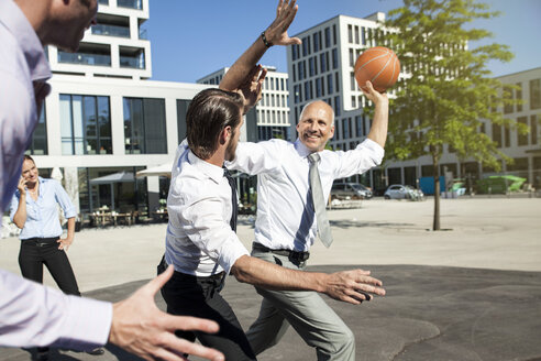Group of businesspeople playing basketball outdoors - SU000028