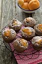 Muffins with bowl of apricots and napkin on wooden table, close up - OD000320