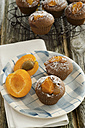 Chocolate muffins on cooling rack with apricot on wooden table, close up - OD000314